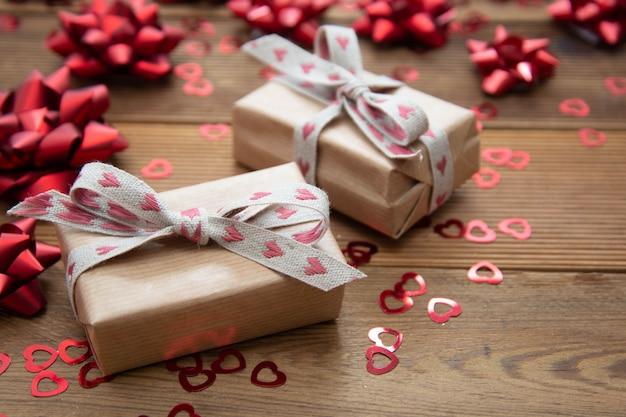 Kraft bruine papieren geschenkdoos met rode strikken en confetti, op houten tafel. valentijnsdag, verjaardag. Premium Foto