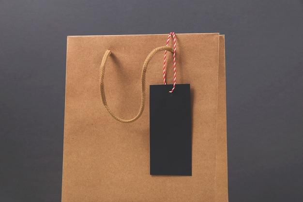 Kraft papieren zak met zwarte vrijdag aankoopetiket op heldere donkere ondergrond. Premium Foto