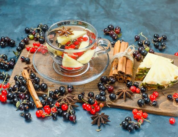 Krenten met kruiden, ananas, drinken hoge hoekmening op donkerblauw en snijplank Gratis Foto