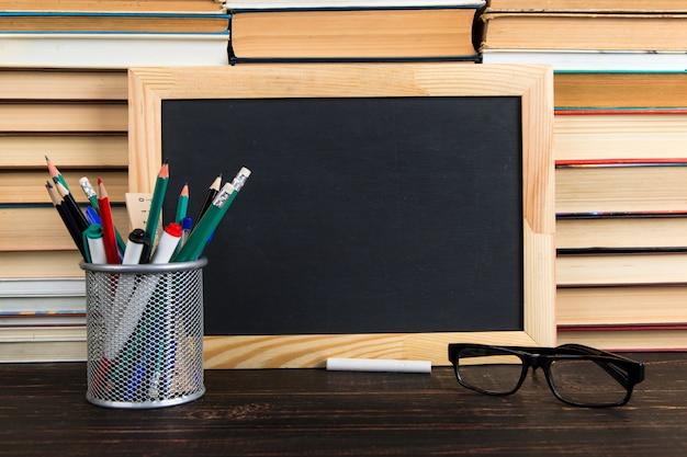 Krijtbord, glazen, standaard met pennen, potloden en krijt, tegen boeken, exemplaarruimte. Premium Foto