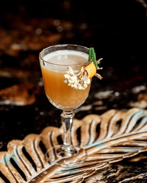 Kristalglas cocktail gegarneerd met bloem en sinaasappelschil Gratis Foto