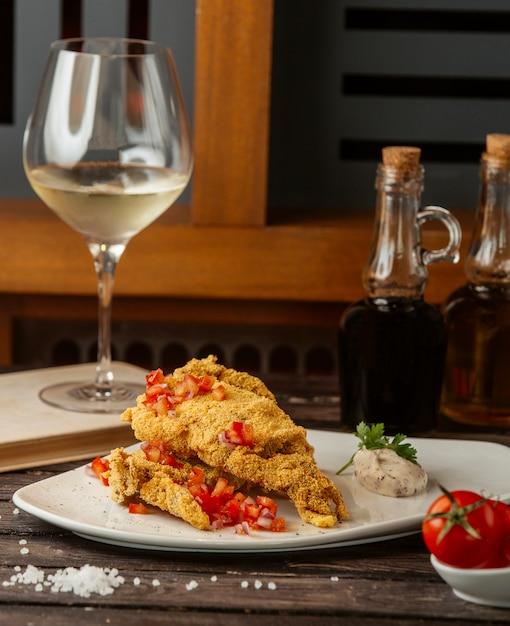 Krokant gebakken vis gegarneerd met tomatenblokjes, geserveerd met kruidensaus Gratis Foto