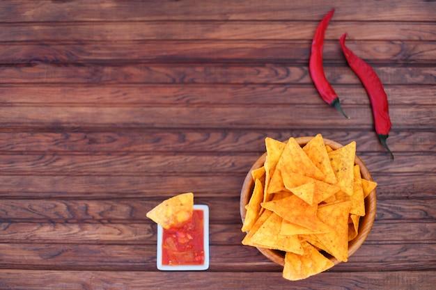 Krokante gouden maïstortilla's met hete salsasaus en een roodgloeiende chili peper voor een pittige snack Premium Foto