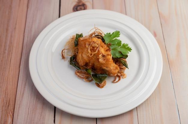 Kruid gebakken kip op een witte plaat op een houten vloer. Gratis Foto