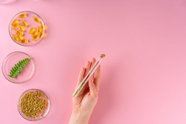 Kruiden en kruiden voedingssupplementen bovenaanzicht op roze achtergrond Premium Foto