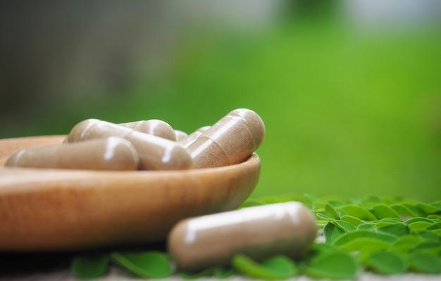 Kruidengeneesmiddelpoeder met capsules voor gezond eten van veel kruiden Premium Foto