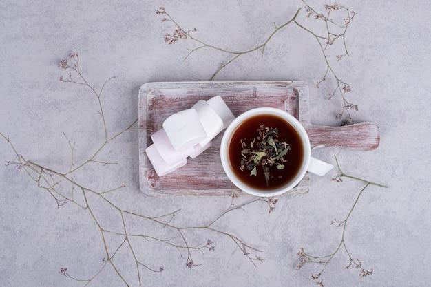Kruidenthee en plaat van marshmallows op grijze achtergrond. hoge kwaliteit foto Gratis Foto