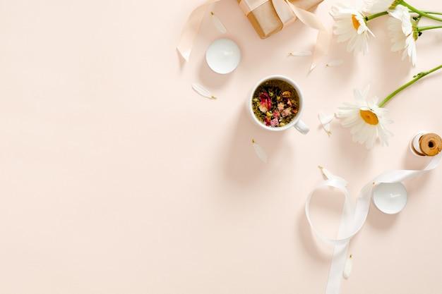 Kruidenthee, kaarsen, lint, geschenkdoos, kamille bloem op pastel roze achtergrond. Premium Foto