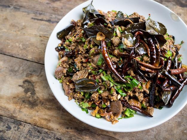 Kruidige eendsalade met groenten en spaanse pepers op houten achtergrond, thaise stijl Premium Foto