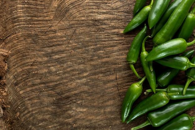 Kruidige groene paprika op houten achtergrond Gratis Foto