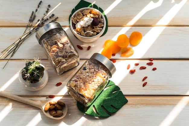 Kruik granola en cornflakes dichtbij droge vruchten op houten achtergrond Gratis Foto