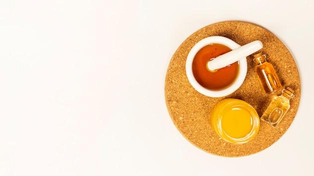 Kruik honing en etherische olie op bruine cork over witte achtergrond Gratis Foto