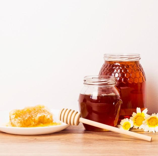 Kruik honing en honingraat met honingsdipper op houten lijst Gratis Foto