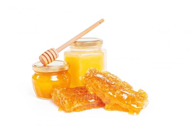 Kruik honing en stok op wit wordt geïsoleerd dat Premium Foto