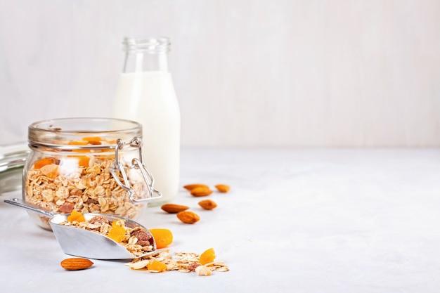 Kruik met zelfgemaakte muesli met noten en gedroogde vruchten en amandelmelk. gezond dieetontbijt Premium Foto