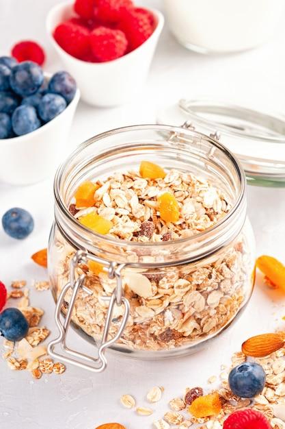 Kruik met zelfgemaakte muesli of havermoutmuesli met noten, gedroogde vruchten en verse bessen. Premium Foto