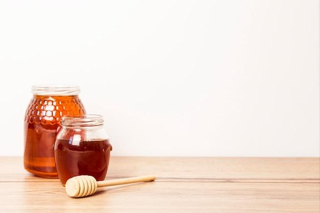 Kruik twee honing met honingsdipper op houten bureau Gratis Foto