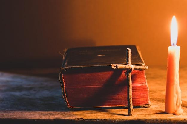 Kruis met bijbel en kaars op een oude eikenhouten tafel. mooie gouden achtergrond. Premium Foto