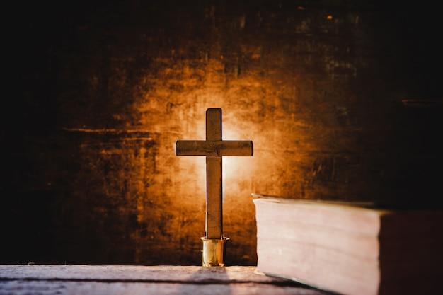 Kruis met bijbel en kaars op een oude eikenhouten tafel. Gratis Foto