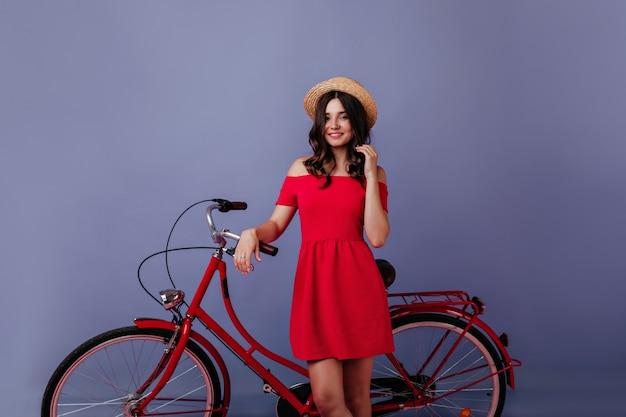 Krullend bruinharig meisje in hoed die zich voor haar fiets bevindt. binnen schot van aangename blanke dame met fiets poseren op paarse muur. Gratis Foto