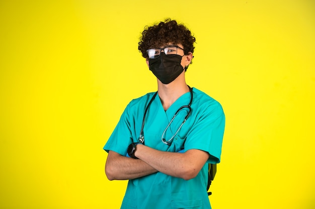 Krullend haarjongen in medisch uniform en gezichtsmasker dat zich in een zekere positie bevindt. Gratis Foto