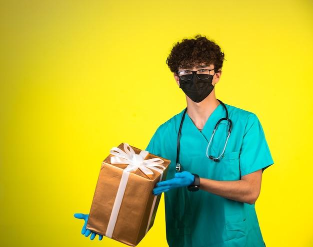 Krullend haarjongen in medisch uniform en gezichtsmasker met een geschenkdoos Gratis Foto