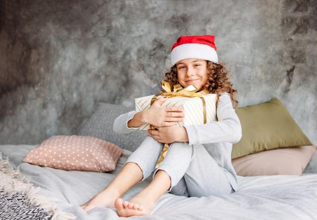 Krullend haired mooi tween-meisje in kerstmanhoed en pyjama's die op bed met grote giftdoos zitten, de tijd van de kerstmisochtend Premium Foto