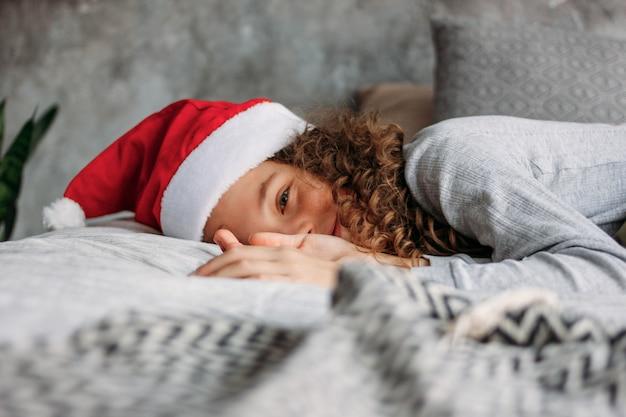 Krullend haired mooi tween-meisje in kerstmanhoed en pyjama's die op bed met hoofdkussen zitten, de tijd van de kerstmisochtend Premium Foto