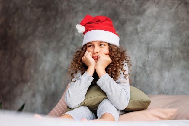 Krullend haired mooi uhappy tween-meisje in kerstmanhoed en pyjama's die op bed met hoofdkussen zitten, de tijd van de kerstmisochtend Premium Foto