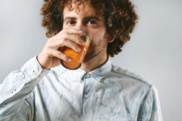 Krullend jonge bebaarde man in wit spijkerbroek shirt drinkt vers geperst natuurlijk sap van biologische boerenwortelen. Gratis Foto