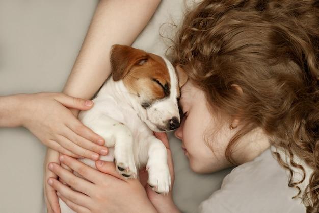 Krullend meisje en de handen van de kinderen knuffelen een puppy Premium Foto