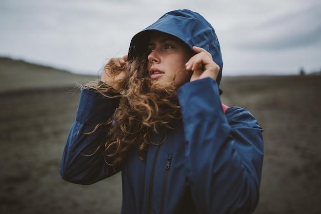 Krullend model dat op het strand staat en geniet van de koude herfstdag met een capuchon over haar hoofd Gratis Foto