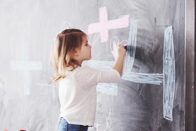 Krullend weinig babymeisje dat met kleurpotloodkleur op de muur trekt. werk van kind. leuke leerling die op bord schrijft Premium Foto
