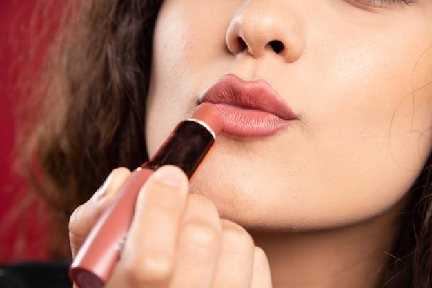 Krullende vrouw die lippenstift toepast. Gratis Foto