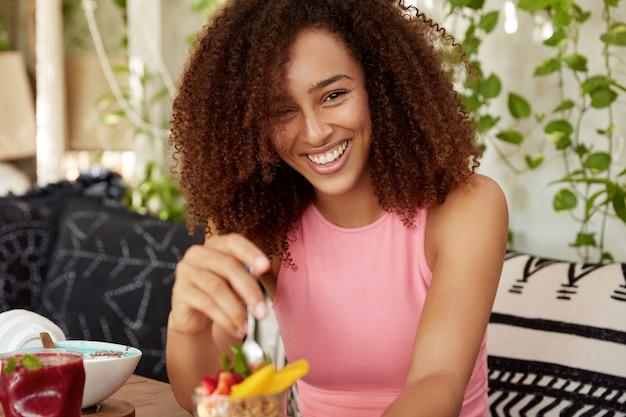 Krullende vrouw met vrolijke uitdrukking, eet heerlijk dessert, in een goed humeur, brengt vrije tijd door in een gezellige koffieshop, geniet van smakelijke fruitsalade. aantrekkelijk vrouwtje rust alleen na een excursie Gratis Foto
