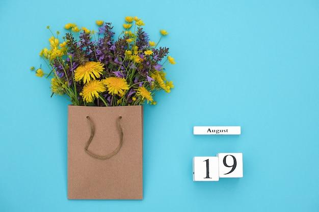 Kubussen kalender 19 augustus en veld kleurrijke rustieke bloemen in ambachtelijke pakket op blauwe achtergrond Premium Foto