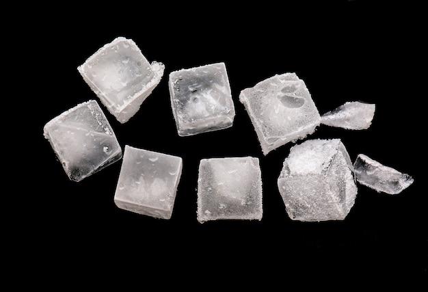 Kubussen van ijs geïsoleerd op zwart, stukken gemalen ijs met sneeuw op de top Premium Foto