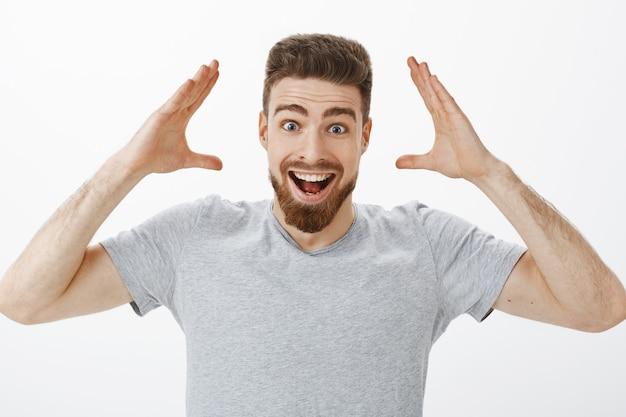 Kun je je voorstellen dat ik een baan heb? charismatisch, vrolijk en opgewonden knap mannelijk model met baard in grijs t-shirt handen opsteken in de buurt van hoofd glimlachend breed goed nieuws ontvangen en het vrienden gelukkig opnieuw vertellen Gratis Foto