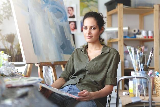 Kunst, werk, inspiratie en creativiteit. portret van mooie getalenteerde jonge brunette vrouw kunstenaar in jeans en shirt van kaki kleur zit op haar atelier voor canvas, bezig met schilderen, Gratis Foto