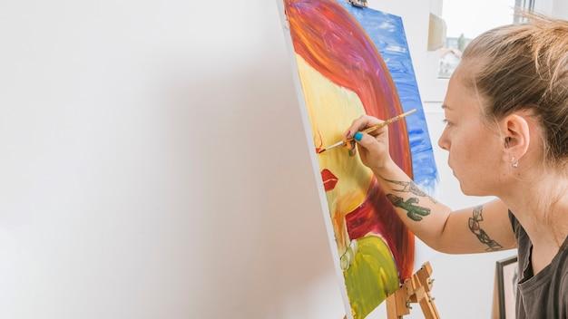 Kunstenaar die beeld trekt op schildersezel Gratis Foto