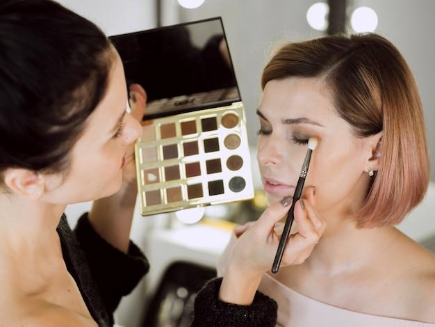 Kunstenaar die make-up op model toepast Gratis Foto