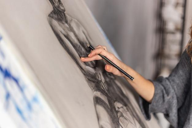 Kunstenaar het schilderen op schildersezel in studio. vrouwelijke schilder die van kant wordt gezien. Premium Foto