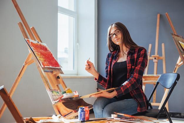 Kunstenaar met een penseel in zijn hand en tekent een afbeelding op canvas Premium Foto