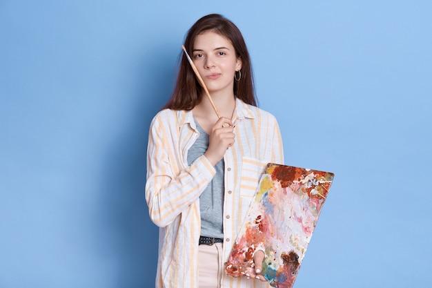 Kunstenaar schetst beeld, poseren met peinzende uitdrukking, brunette dame wit overhemd met penseel in handen dragen. Gratis Foto