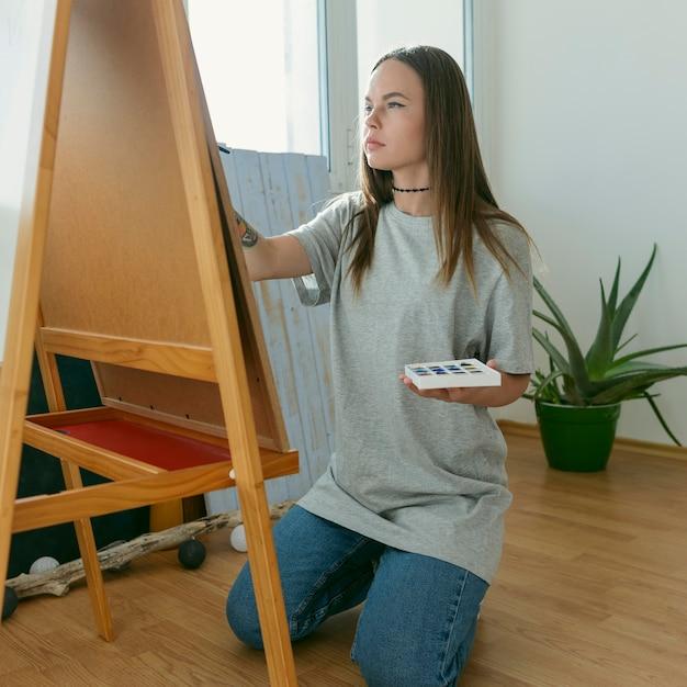 Kunstenaar vrouw schilderij op canvas zijaanzicht Gratis Foto