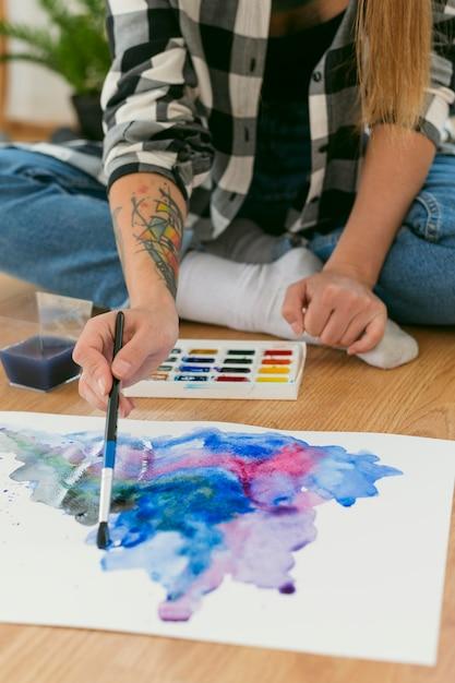 Kunstenaar vrouw schilderij op de hoge mening van de vloer Gratis Foto