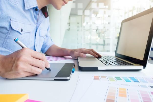 Kunstenaarstekening iets op grafische tablet op het kantoor. Premium Foto