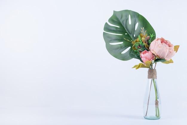 Kunstmatige blad en bloemen in glazen pot op wit oppervlak. Gratis Foto