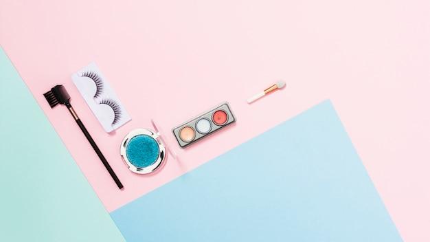 Kunstmatige wimpers; oogschaduw palet en make-up borstel op triple gekleurde achtergrond Gratis Foto