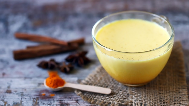 Kurkumamelk met kruiden in een mok. gouden kurkumamelk. indiase gezondheidsdrank. selectieve aandacht. Premium Foto